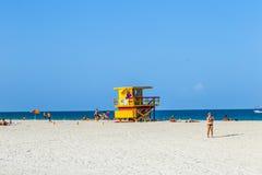 人们在救生员塔旁边享用海滩 免版税库存图片