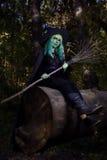 有绿色头发和笤帚的女孩在巫婆衣服森林万圣夜时间的 免版税库存照片
