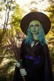 Νέο κορίτσι με την πράσινη τρίχα και σκούπα στο κοστούμι της μάγισσας στο δασικό χρόνο αποκριών Στοκ εικόνες με δικαίωμα ελεύθερης χρήσης