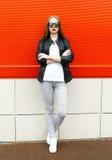 在城市塑造佩带岩石黑色的时髦的俏丽的妇女皮夹克和太阳镜 免版税库存照片
