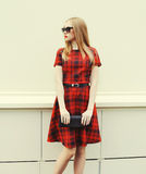 红色礼服的,有提包传动器的太阳镜美丽的白肤金发的妇女 免版税图库摄影