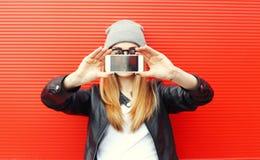 拍在智能手机自画象的行家凉快的女孩照片 免版税库存图片