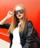 佩带岩石黑色皮夹克、太阳镜和袋子在红色的画象时尚俏丽的妇女 免版税库存照片