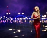 时尚妇女夜城市,式样女孩红色礼服,街灯 免版税库存照片