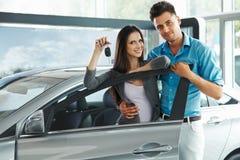 庆祝一辆汽车的购买的年轻夫妇在汽车陈列室里 库存照片