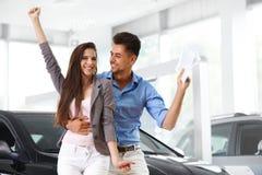 庆祝一辆汽车的购买的年轻夫妇在汽车陈列室里 免版税库存照片
