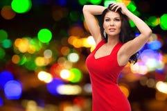 红色礼服的美丽的妇女在夜点燃 免版税库存图片