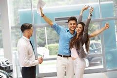 庆祝一辆汽车的购买的年轻夫妇在汽车陈列室里 免版税库存图片