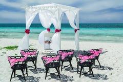 婚礼惊人的华美的邀请的看法装饰了与老葡萄酒黑色金属椅子的眺望台在海滩 免版税库存照片