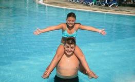 愉快的快乐的使用在与自然海洋的游泳池的十几岁的男孩和小俏丽的女孩浇灌 免版税库存图片
