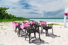 Η άποψη του γάμου διακόσμησε τις παλαιές εκλεκτής ποιότητας αναδρομικές μαύρες καρέκλες που στέκονται στην τροπική παραλία Στοκ Φωτογραφίες
