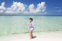 走沿海滩和平静的美丽的海洋的相当被称呼的逗人喜爱的小女孩在她的手上拿着面包 免版税库存照片