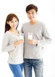 年轻微笑的夫妇饮用奶 免版税库存图片