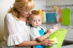 母亲和孩子儿子洗涤的盘 免版税库存照片