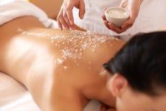 温泉妇女 得到盐的浅黑肤色的男人洗刷在的秀丽治疗 免版税库存图片