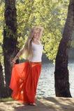 美好的年轻白肤金发的妇女跳舞在河岸的树下 免版税库存图片