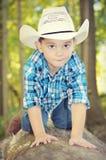 爬行在树干的男孩 免版税库存图片