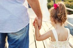 手拉手举行在日落的父亲和小女儿 免版税库存照片