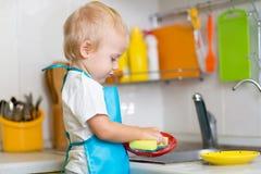 儿童洗涤的盘在一个国内厨房里 免版税库存图片