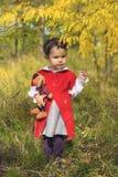 有她的兔宝宝玩具的小女孩在森林里 库存图片