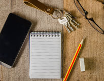 空白的笔记薄、钥匙链、眼睛玻璃和手机在木 图库摄影