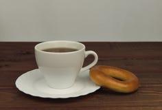 在一杯木桌茶和新面孔百吉卷饼干上 免版税库存图片