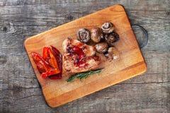 Ψημένα στη σχάρα κρέας και λαχανικά στον τέμνοντα πίνακα Στοκ Εικόνες