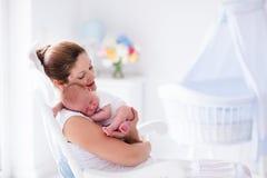 母亲和新出生的婴孩在白色托儿所 库存图片