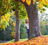 美丽的少妇在掩藏在树后的秋天公园 图库摄影