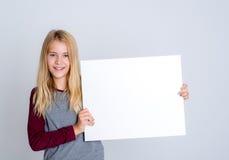 显示一个白色标志的好白肤金发的女孩 免版税库存图片