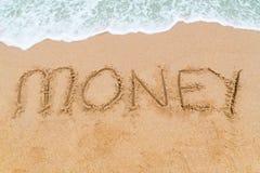在与波浪接近的沙滩写的金钱题字 免版税库存图片