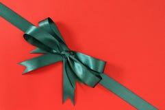 在红色纸背景的绿色礼物丝带弓角落对角线 免版税库存图片