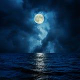 在云彩的超级月亮在水 库存照片