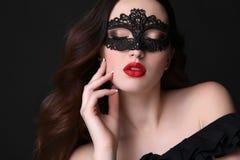 Όμορφη γυναίκα με την πολυτελή σκοτεινή τρίχα, με τη μάσκα δαντελλών στο πρόσωπο Στοκ Εικόνα