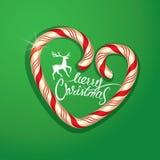 在棒棒糖心脏形状的圣诞节框架在绿色背景 库存照片