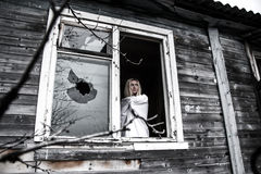 Γυναίκα που μένει κοντά στο σπασμένο παράθυρο Στοκ Φωτογραφίες