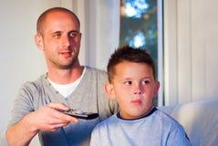 放松在聪明的电视前面的愉快的家庭 免版税库存照片