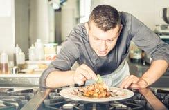 准备一顿鲜美膳食的年轻厨师 免版税图库摄影