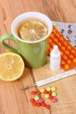 Пилюльки, падения носа и горячий чай с лимоном для холодов, обработка гриппа и жидкое Стоковая Фотография