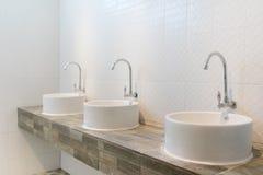 三个白色水槽在卫生间里 库存图片