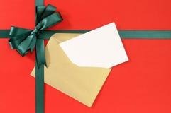 开放圣诞节或生日贺卡,在简单的红色纸背景的绿色礼物丝带弓 免版税库存图片