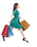 跳跃与购物袋的妇女的侧视图 免版税库存照片