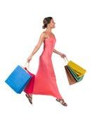 跳跃与购物袋的妇女的侧视图 免版税图库摄影