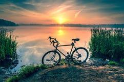 在湖的自行车日出的 免版税图库摄影