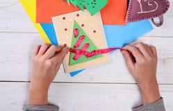 关闭在做圣诞树的儿童的手上由色纸 孩子艺术,艺术射出,手工制造新年装饰 免版税库存照片