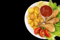 在一块白色板材的鸡腿有在黑背景蕃茄和莴苣和炸薯条和番茄酱顶视图隔绝的切片的 免版税库存图片