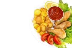 在一块白色板材的鸡腿有在黑背景蕃茄和莴苣和炸薯条和番茄酱顶视图隔绝的切片的 免版税库存照片