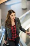 在购物中心射击的有吸引力的少妇时尚 黑皮夹克的美丽的时兴的女孩在购物中心的自动扶梯 免版税库存图片