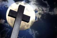 反对月亮的石十字架,在夜空的剧烈的云彩 免版税库存图片