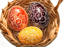 在被编织的篮子的三个复活节彩蛋 图库摄影